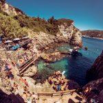 spiaggia della grotta di Paleokastritsa a corfù: ragazzi si tuffano durante un viaggio evento di maturità
