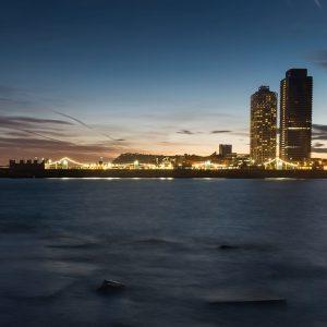 La Barceloneta di notte con le torri del porto a Destra.