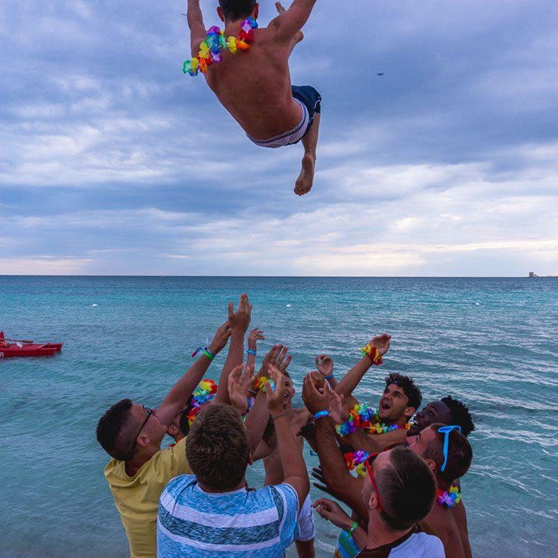 un gruppo di ragazzi lancia in acqua un amico durante le vacanze per giovani College